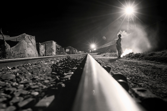A raw of nylon and cardboard houses stretches along the railway. A lady starts a fire to obliterate the pressing cold of the night. Madagascar 2016 ©
