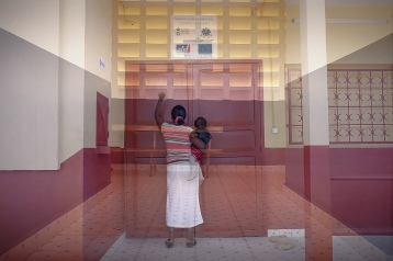 madame Vonjy avec son enfant devant une porte fermée du centre de santé de base (CSB II). c'est le weekend à Tuléar, les patients sont redirigés vers le CHU situé à plus de 2Km, Pourquoi?
