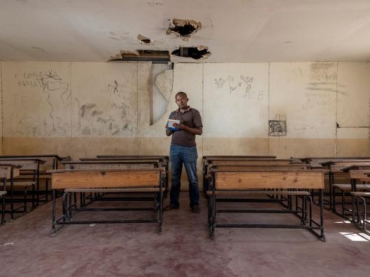 José, un journaliste, posant dans une salle de classe délabrée qui est en face du centre de santé de base. son travail consiste à exposer la Réalité de façon objective afin d'éveiller les consciences pour que le peuple puisse prendre des décisions éclairées en matière d'hygiène, de santé, de nutrition et d'envi- ronnement.