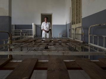dr. Ravaomalala, médecin assistant, posant derrière des lits détériorés et inconfortables. présent et toujours prêts à accomplir l'impossible avec le peu de moyens à leur disposition, les agents de santé prodiguent des soins malgré ce manque d'Équipement.